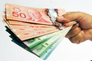 Hand holding fanned out Canadian money.The Canadian Press Images-Mario Beauregard